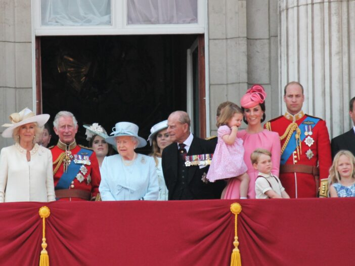 The royal family on a balcony at Buckingham Palace, including Queen Elizabeth, Prince Philip, Prince Charles, Prince William, Kate Middleton, and their children.