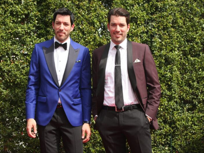 The Scott brother in tuxedos in front of an ivy wall.