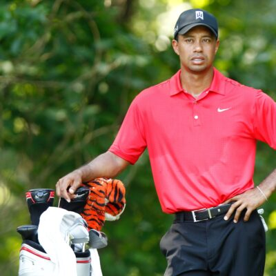 Tiger Woods in a bright red Nike polo resting one arm on his hip and the other on his clubs with a serious expression on his face.