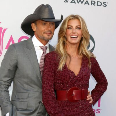 Tim McGraw, in a gray suit and cowboy hat poses with wife Faith Hill, in a red leopard print dress