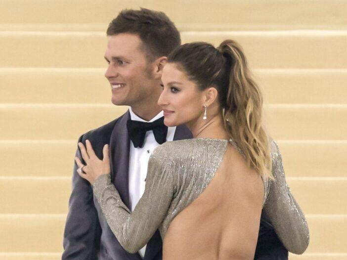 Tom Brady in a tuxedo smiling with wife Gisele Bundchen in a silver dress