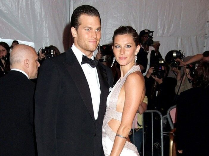 Tom Brady wearing a black tux poses with Gisele Bundchen, in an ivory dress, at the Met Gala