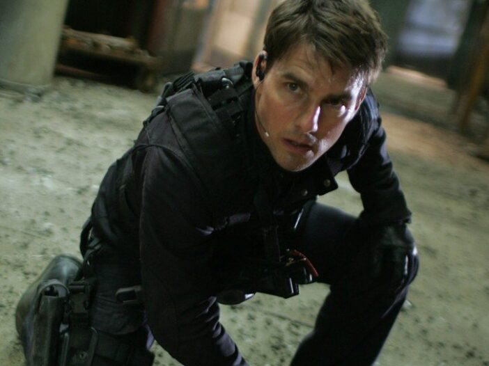 Tom Cruise crouching down in all black in a screenshot from the Mission Impossible movies.