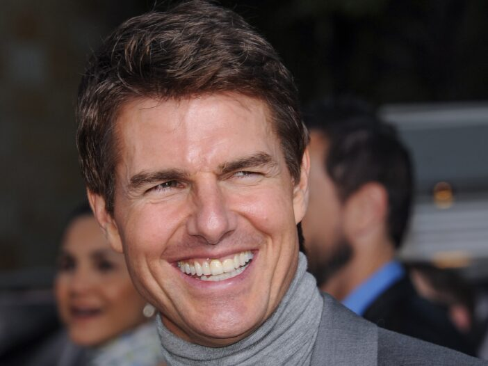 Tom Cruise smiling and wearing gray turtleneck suit in 2013