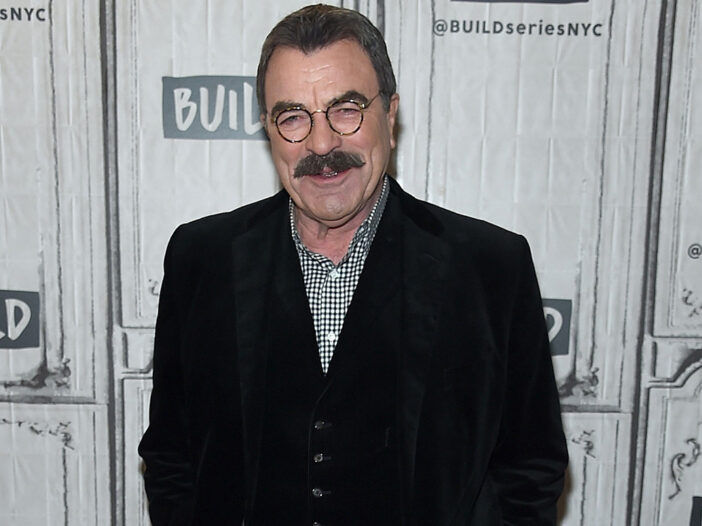 Tom Selleck smiling in a dark jacket and checkered shirt.