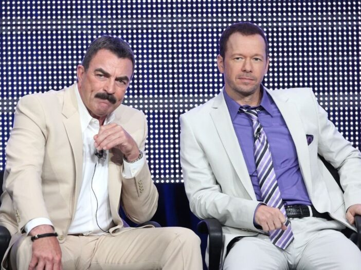 Tom Selleck wearing a beige suit sitting with Donnie Wahlberg, wearing a white suit, during a Blue B