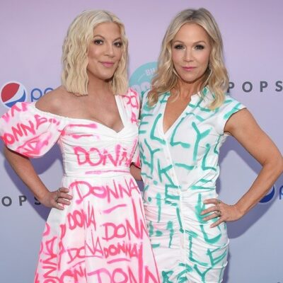 Tori Spelling and Jennie Garth pose on the red carpet wearing gowns featuring their 90210 names