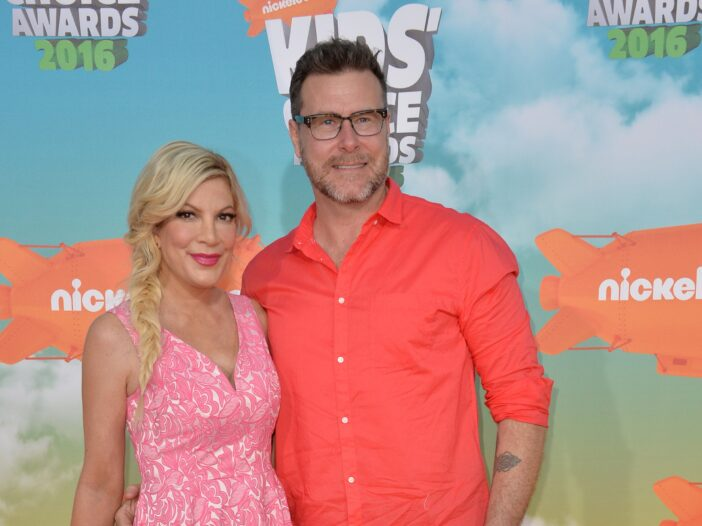 Tori Spelling in a pink dress on the left, standing with Dean McDermott on the right, wearing an orange shirt.
