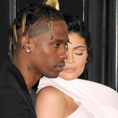 Travis Scott, in a black suit, holds Kylie Jenner, in pink, close to his chest on the red carpet