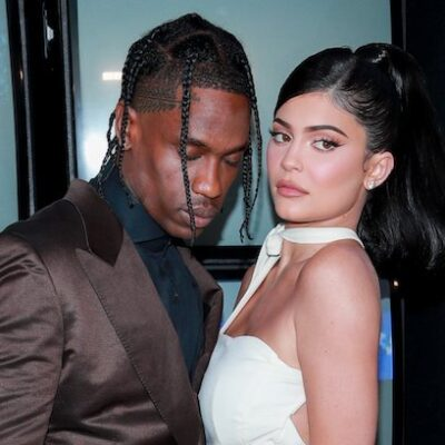 Travis Scott in a chocolate brown suit with a black shirt and Kylie Jenner in a white dress together