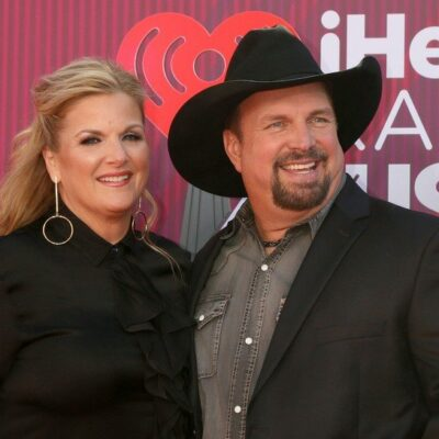 Trisha Yearwood in a black blouse smiling with Garth Brooks in a black suit