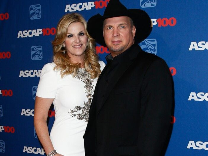 Trisha Yearwood on the left, in a white dress, Garth Brooks on the right in a dark suit and cowboy hat.