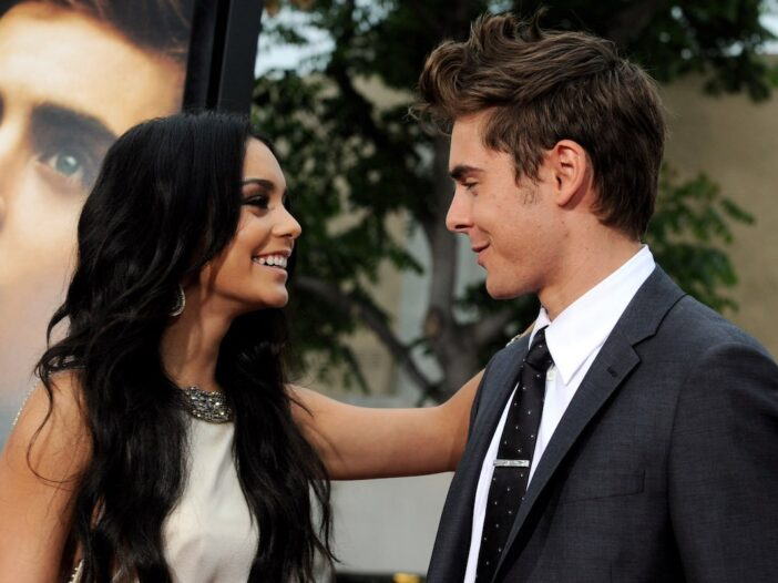 Vanessa Hudgens in a tan dress smiles and rests her arm on a smiling Zac Efron in a grey suit