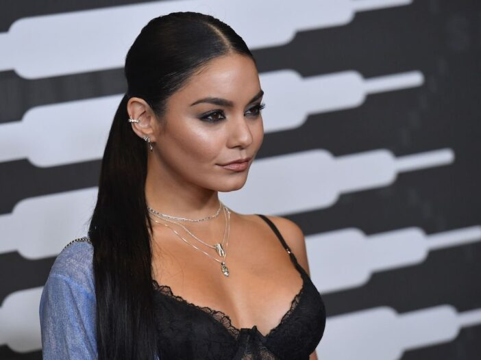 Vanessa Hudgens smiles off camera in a loose blue shirt on one shoulder and a black lacy top