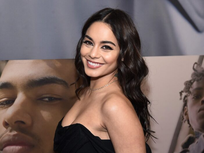 Vanessa Hudgens turns and smiles at the camera in a black dress at the West Side Story opening