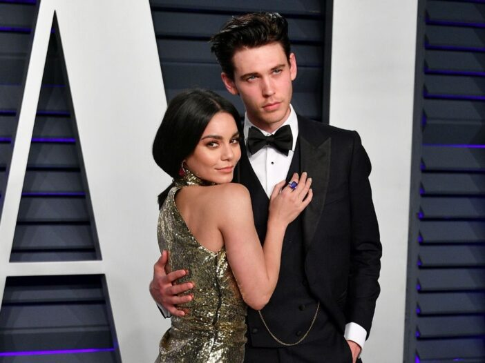 Vanessa Hudgens wearing a gold dress standing with Austin Butler, who's wearing a black tux, on the