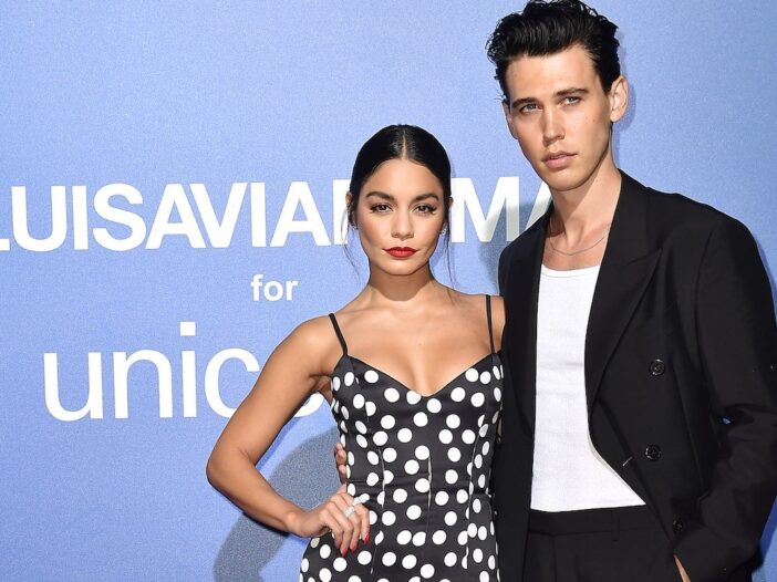 Vanessa Hudgens with a hand on her hip in a black and white dress and Austin Butler in a black jacke