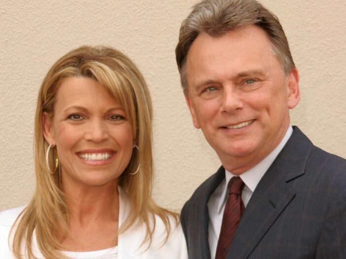 Vanna White smiling in a white outfit with Pat Sajak in a suit