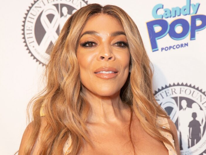 Wendy Williams wearing a low cut pale peach dress on the red carpet.