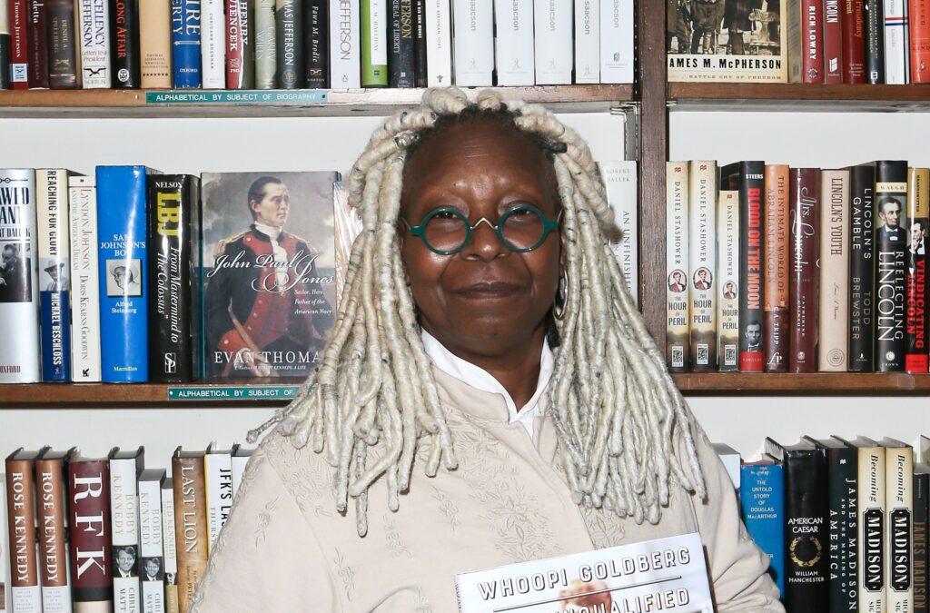 Whoopi Goldberg holds a book aloft as she stands against a bookshelf