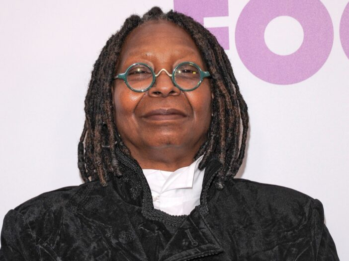 Whoopi Goldberg stands against a white background while wearing a black jacket