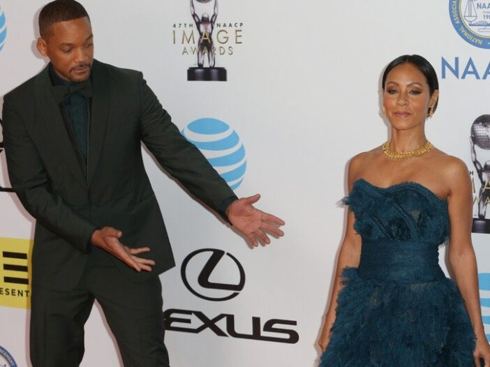 Will Smith, wearing a black suit and gesturing at his wife, Jada Pinkett Smith, who's wearing a dark