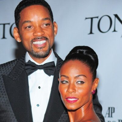 Will Smith wearing a black tux standing with his wife, Jada Pinkett, at a red carpet event.