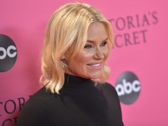 Yolanda Hadid smiling in a dark sweater, in front of a pink background.