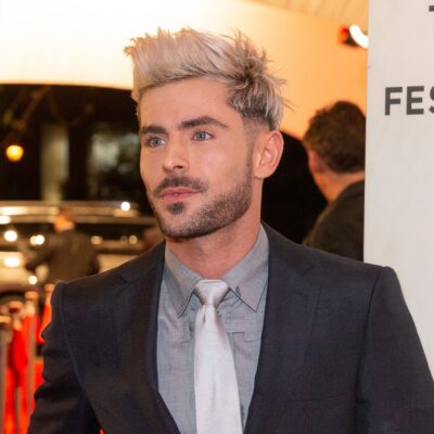 Zac Efron, in a black suit, arrives at the premiere of Extremely Wicked, Shockingly Evil and Vile