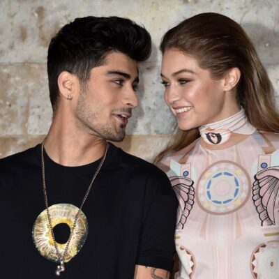 Zayn Malik wearing a black tee shirt standing with Gigi Hadid, who's wearing a multicolored gown, on
