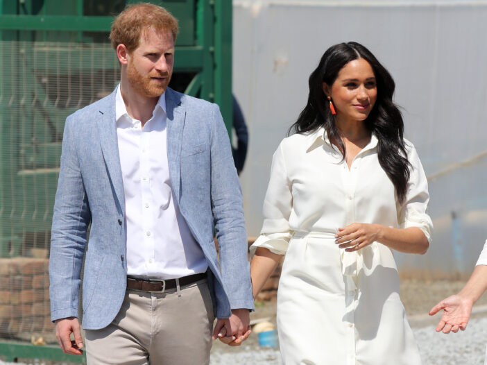 Prince Harry wears a blue jacket and walks with Meghan Markle, in a white dress