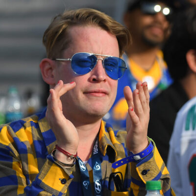 Macaulay Culkin wearing blue sunglass and holding his hands up to shout.