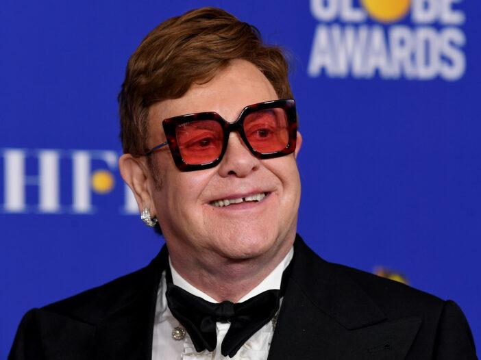 Elton John wearing big red sunglasses