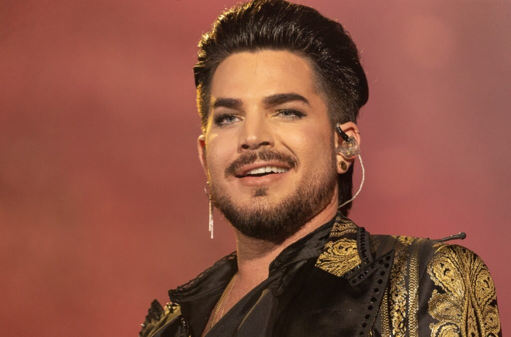 Adam Lambert in a black and gold jacket performing with Queen during the Global Citizen Festival.