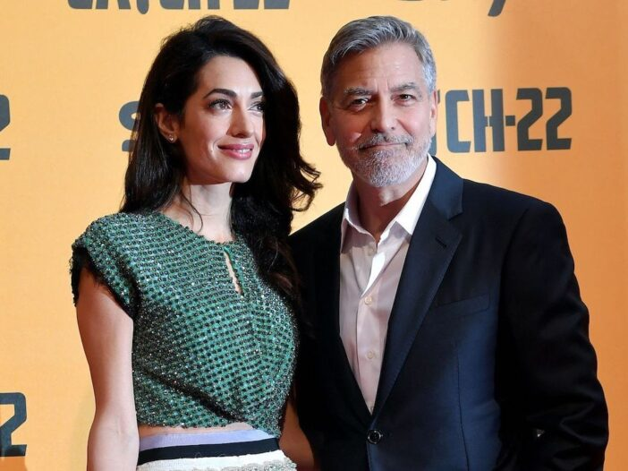 Amal Clooney smiling in a green top with husband George Clooney in a suit.