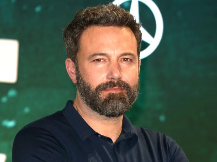 Ben Affleck with a beard and his arms crossed, wearing a blue shirt.