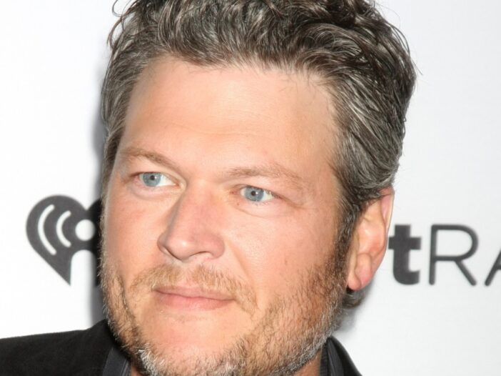 Blake Shelton, wearing a dark jacket, stands against a white background with black lettering
