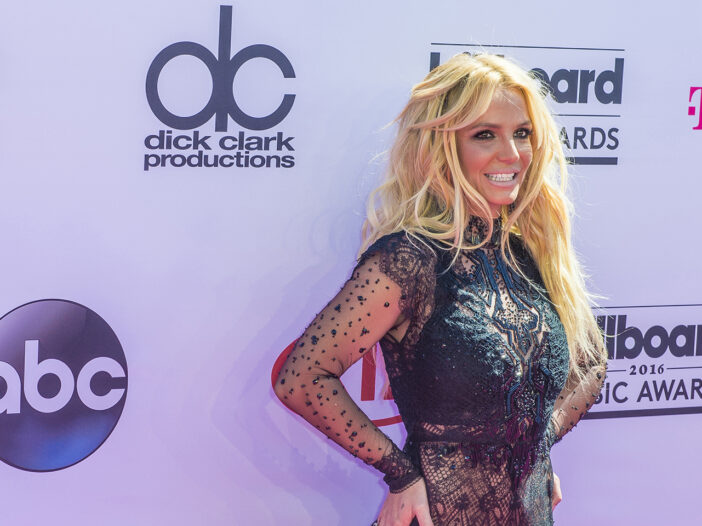 Britney Spears smiling in a revealing dress at a red carpet event.