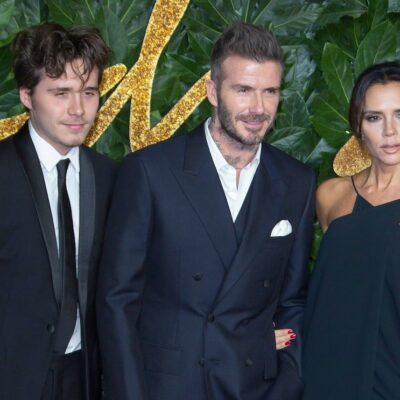 Brooklyn Beckham in a suit with parents David Beckham and Victoria Beckham