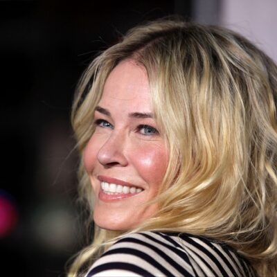 Chelsea Handler, wearing a stripped top, looks over her shoulder and smiles at the camera