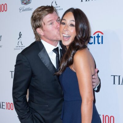 Chip Gaines plants a kiss on Joanna Gaines' cheek as she smiles for the camera