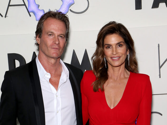 Rande Gerber on the left, standing with Cindy Crawford who's wearing a red dress.