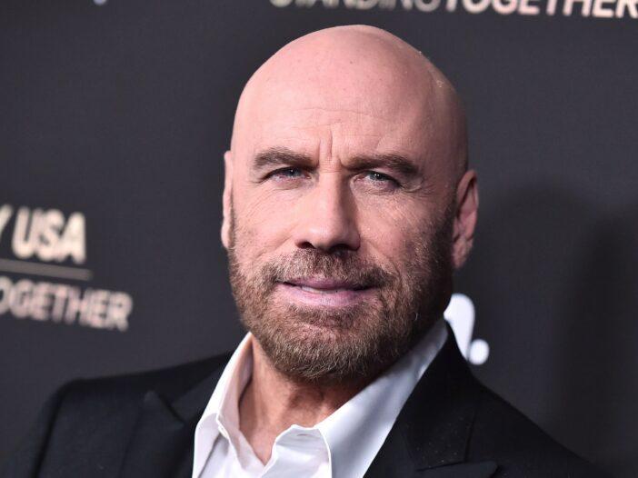 Close up of a bald John Travolta with a beard.