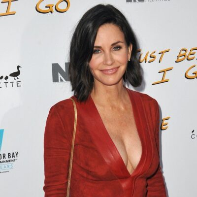 Courteney Cox smiling in a red dress at a red carpet event
