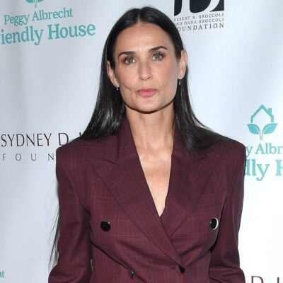 Demi Moore looking at the camera dressed in a maroon suit