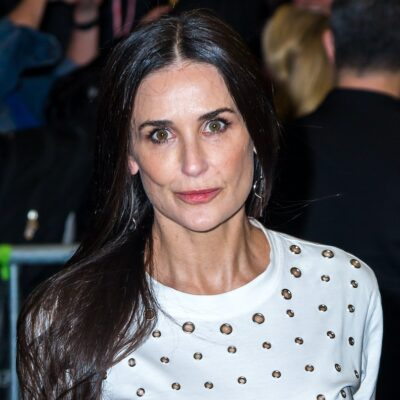 Demi Moore smiling in a white top outside