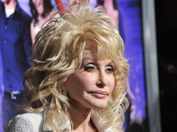 Dolly Parton wears a white jump suit against a purple background