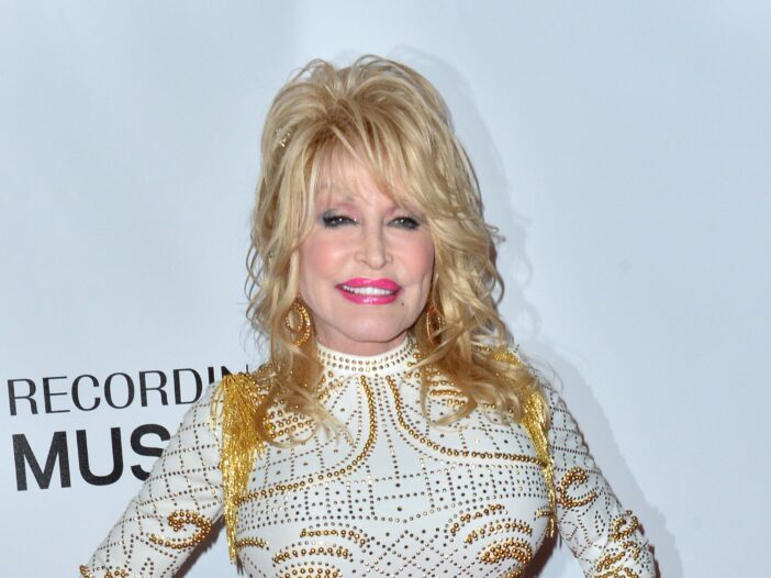 Dolly Parton wearing a white and gold dress at the 2019 MusiCares Person of the Year Gala honoring Dolly Parton at the Los Angeles Convention Centre
