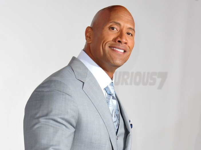Dwayne Johnson wears a light gray suit at the premiere of a movie