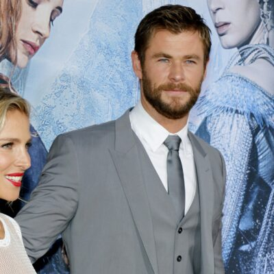 Elsa Pataky, in white, walks with Chris Hemsworth, wearing a gray suit, on the red carpet